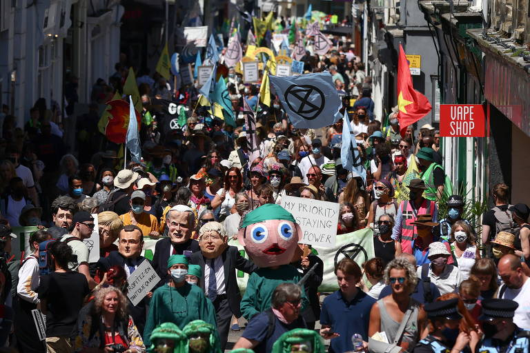 Manifestantes marcham durante ato do movimento Extinction Rebellion na cidade de Falmouth, na Cornualha (sudoeste inglês), durante o G7