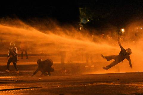 A demonstrator falls as they are hit by water cannon during clashes with riot police amid ongoing protests against the government of Colombian President Ivan Duque in Bogota on June 12, 2021. - Dozens of people have been killed in protests that erupted around the country on April 28, initially against a tax hike that would have mostly affected the middle classes, but which have morphed into a major anti-government movement. (Photo by Juan BARRETO / AFP)