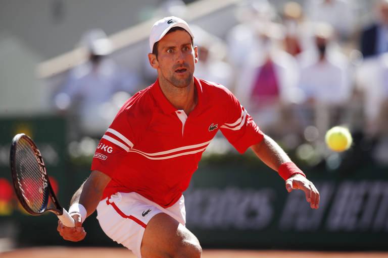 Tenista com camiseta vermelha se abaixa para bater na bola