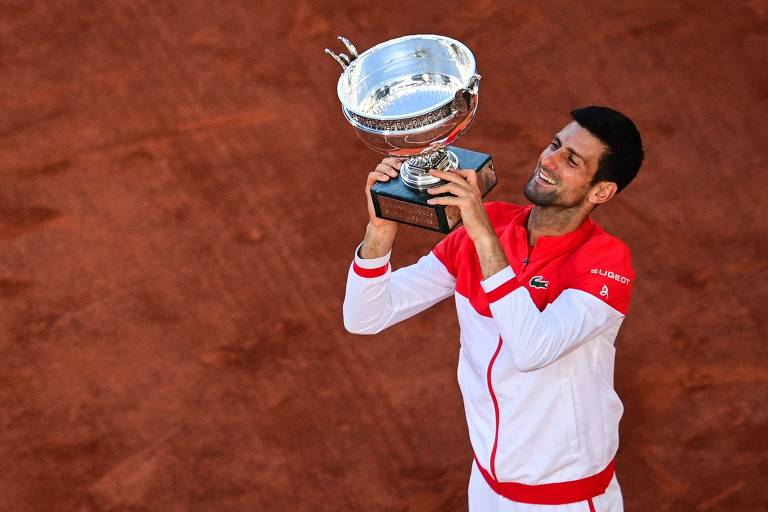 Djokovic olha para o troféu e sorri
