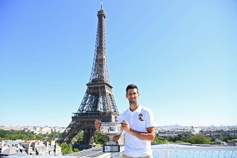 Vestido de branco, homem segura grande taça; ao fundo, Torre Eiffel