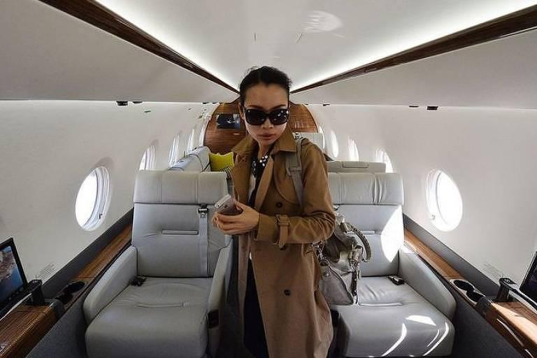 Mulher está em pé em avião de luxo usando óculos escuros e sobretudo marrom