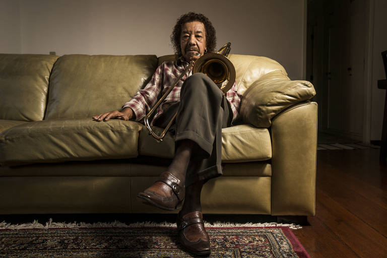 Homem negro sentado em sofá segura um trombone