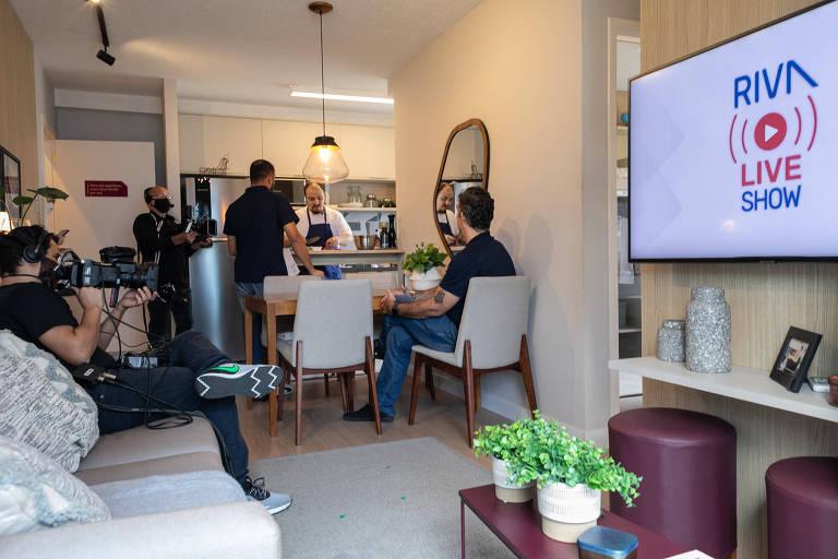 Sala de apartamento com pessoas sentadas de costas e câmeras filmando