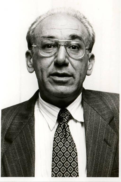 imagem em preto e branco de homem de terno, gravata e óculos