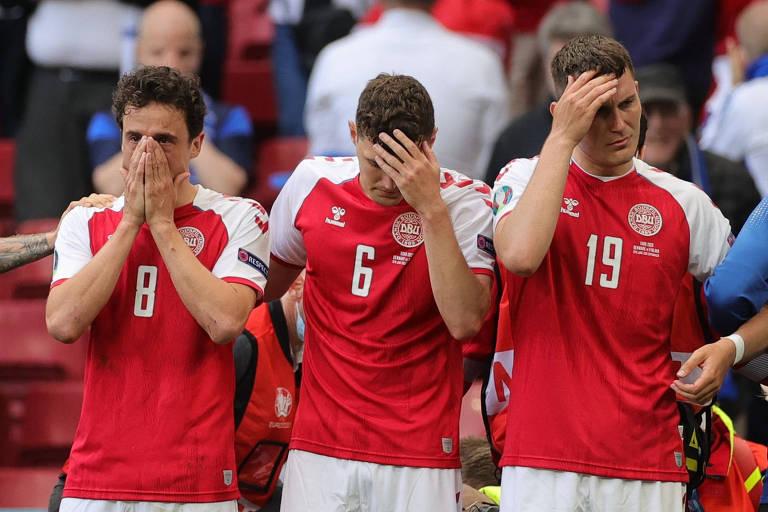 Jogadores da seleção da Dinamarca preocupados enquanto Eriksen recebe atendimento
