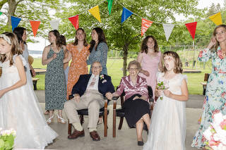 Joy Morrow-Nulton and John Shults Jr. are surrounded by family and friends on their wedding day in Ulster, N.Y., May 22, 2021. (Lauren Lancaster/The New York Times)