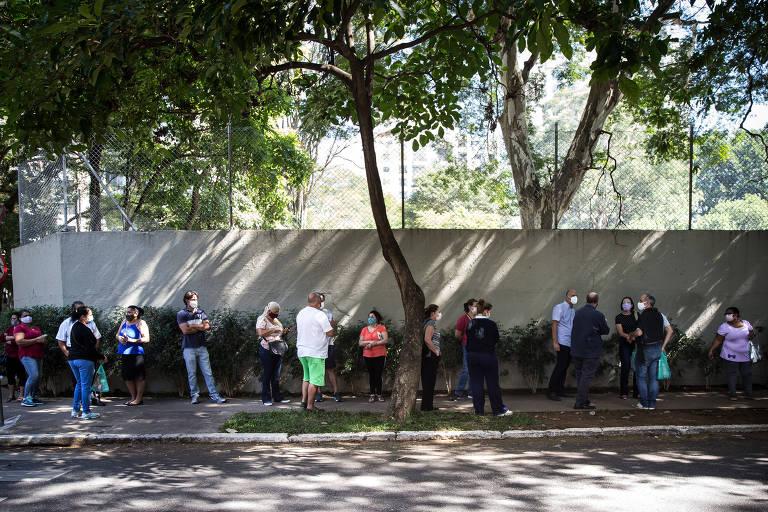Pessoas aguardam alinhadas em fila paralela a muro branco e com árvores ao redor