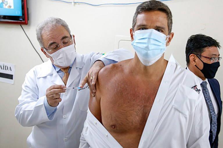 O ministro da Saúde, Marcelo Queiroga, vacina contra o coronavírus o presidente do Banco Central, Roberto Campos Neto, no Distrito Federal