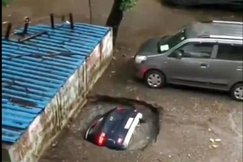 Carro é engolido em buraco de estacionamento