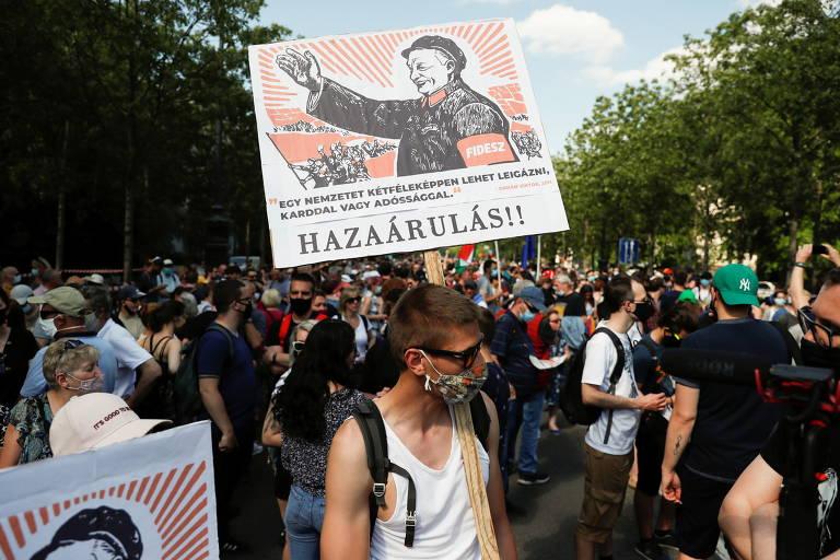 Manifestante segura cartaz que chama o premiê Viktor Orbán de traidor durante o ato em Budapeste