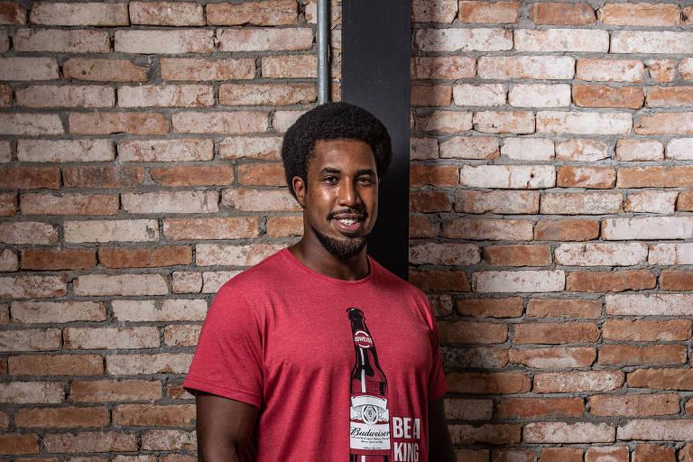 Homem negro de pé em um fundo de parede de tijolos usando calça branca, tênis branco e camiseta vermelha