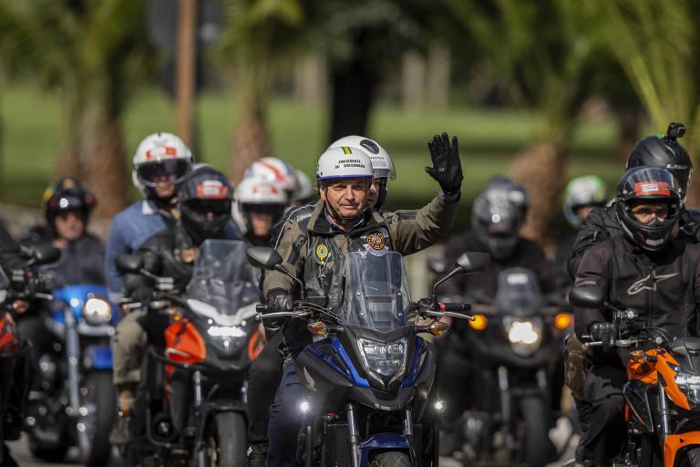 Bolsonaro está no centro da foto, dirigindo uma moto e cercado por outros motociclistas. Ele usa um capacete branco e acena