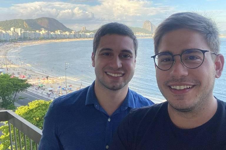 Dois homens brancos em frente a uma paisagem de praia. Um usa óculos e camiseta preta a o outro usa uma pólo azul