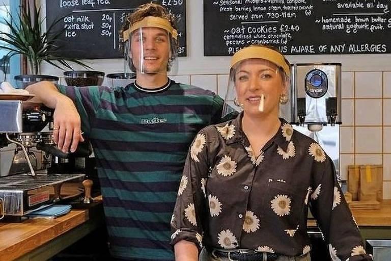 Duas pessoas em um café, sorrindo, usando face shields