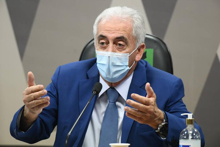 Homem de terno e gravata sentado, com máscara, fala com as duas mãos gesticulando em frente a microfone