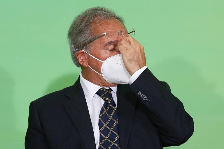 O ministro Paulo Guedes (Economia), de máscara e olhos fechados, com a mão sobre a testa, durante evento em Brasília