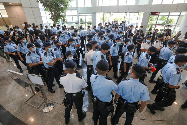 Saguão de prédio totalmente ocupado por aglomeração de pessoas em fardas azuis