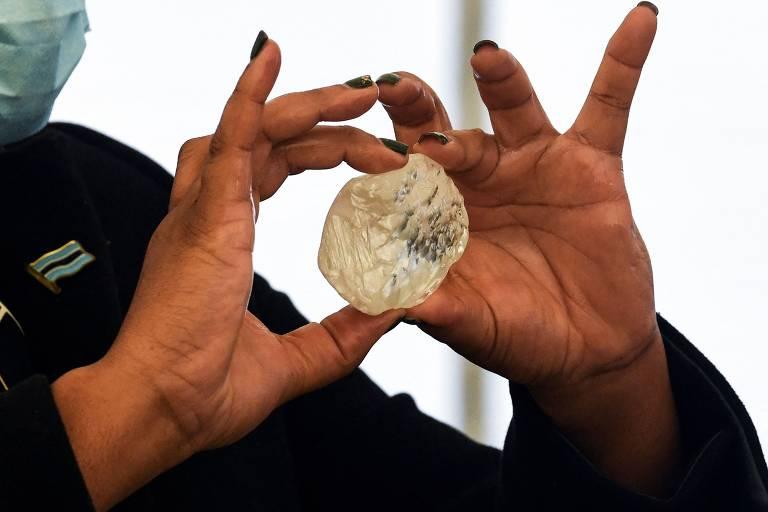 Duas mãos seguram um diamante que tem o tamanho aproximando de um ovo