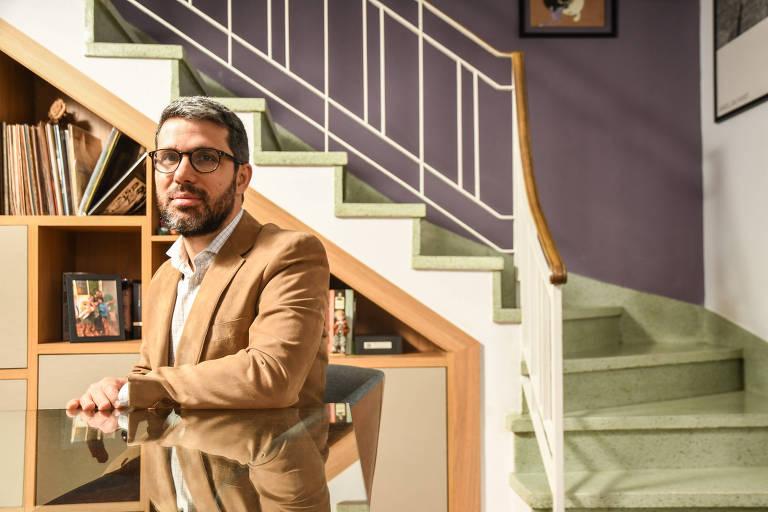 Homem jovem de óculos e barba, vestindo camisa clara e terno bege, com as mãos apoiadas numa mesa de vidro, com uma escada e uma estante ao fundo