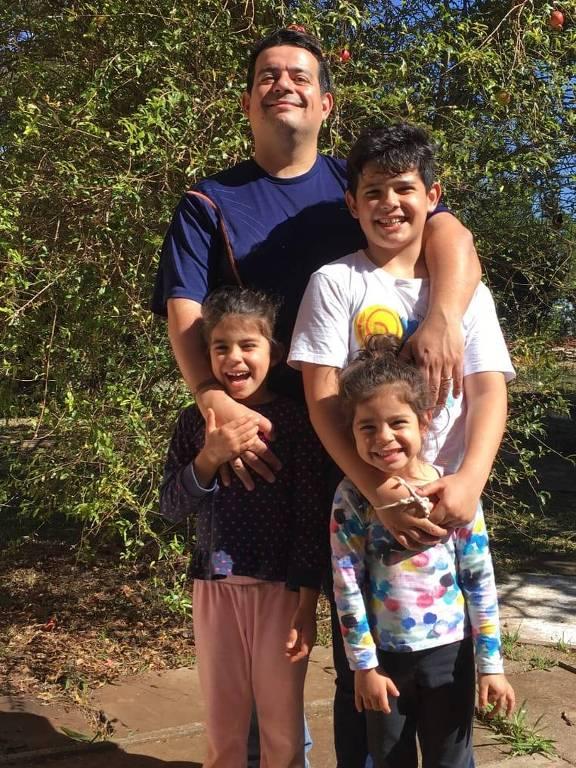 Rodrigo Rizzi, 42, posa para a foto com os três filhos; eles estão abraçados