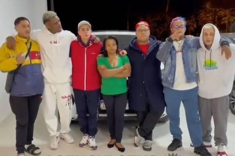 Seis homens e uma mulher ao centro, todos abraçados