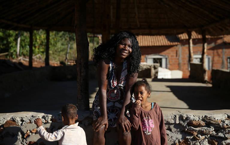 Ao centro, uma mulher negra de cabelos compridos sorri. Aos lados dela estão uma menina que olha para a câmera e um menino de costas