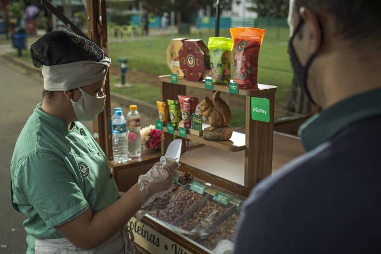 Mulher de máscara atrás de um carrinho de venda de nozes, amendoins e petiscos atendendo um cliente no parque