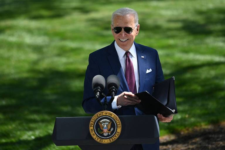 Biden, de camisa branca, paletó azul-marinho e gravata em tom de vermelho e óculos escuros estilo aviador preto, segura pasta enquanto sorri. Ele está em um púlpito e, atrás, há um gramado