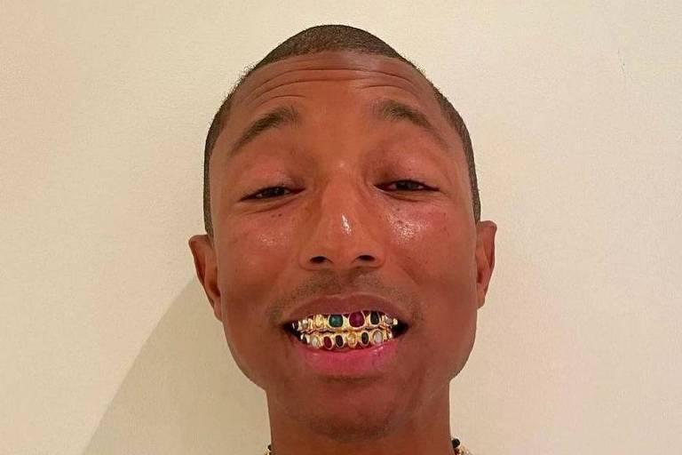 Pharrell Williams com seus grillz de ouro e pedras preciosas