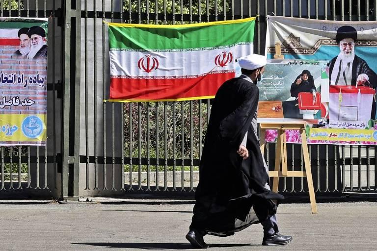 Iraniano passa em frente a cartazes em Teerã encorajando eleitores a votarem na eleição presidencial