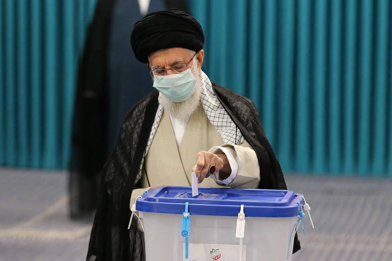 De turbante e máscara, homem deposita papel em urna de plástico