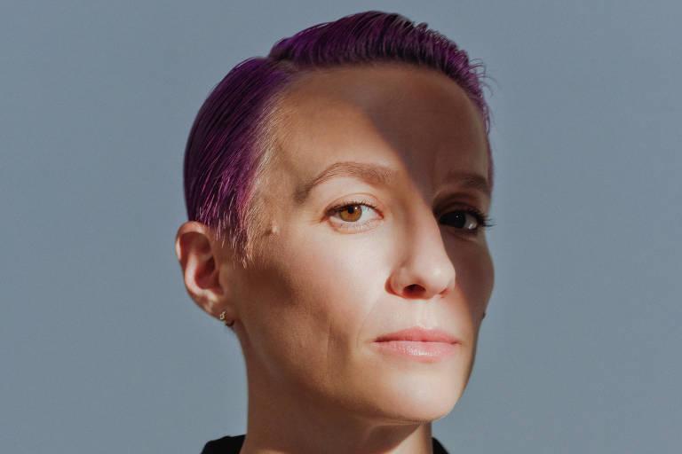 Mulher com cabelo curto e roxo posa séria para a foto