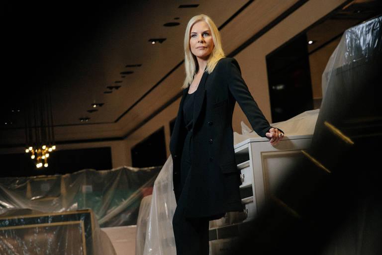 Mulher loira posa em pé para a foto com uma roupa preta