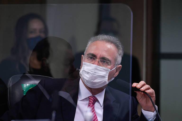 Calheiros de máscara e segurando a ponta de um microfone de mesa com uma das mãos. Ele aparece por trás de um vidro, que reflete o rosto do presidente da CPI, o senador Omar Aziz