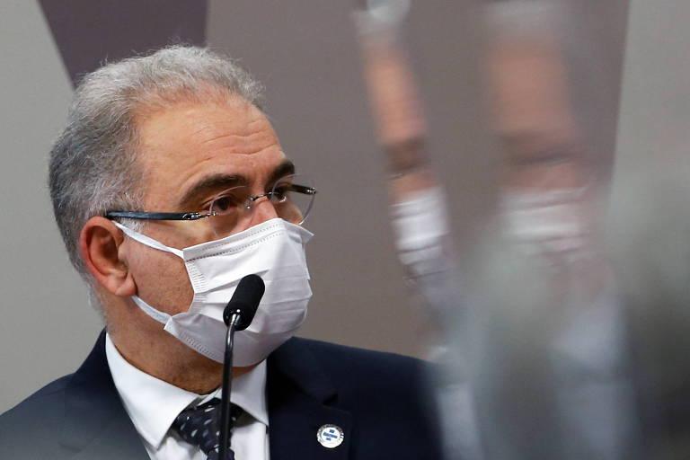 Perfil de Queiroga, que usa máscara e tem rosto refletido em vidro ao lado