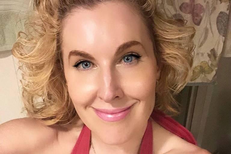 Mulher branca, loira com olhos azuis fazendo selfie enquanto veste a parte de cima de um biquíni rosa