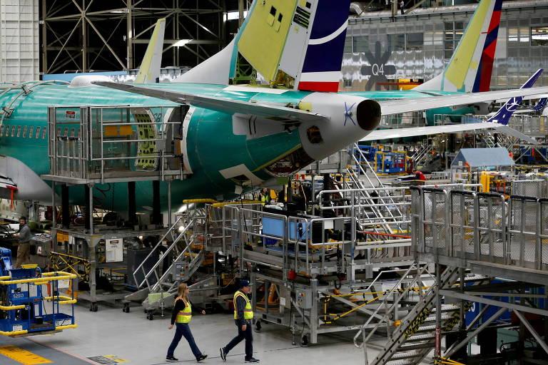 Funcionários caminham próximo a uma aeronave 737 Max na fábrica da Boeing em Washington, nos Estados Unidos