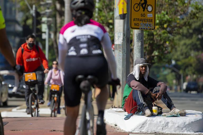 Ciclistas passam por homem negro em colchão na avenida Faria Lima