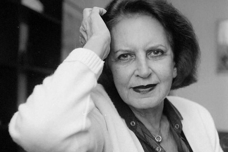 retrato em preto e branco de mulher branca sentada em uma poltrona, apoiando a cabeça em uma das mãos. ela olha para a câmera e sorri levemente