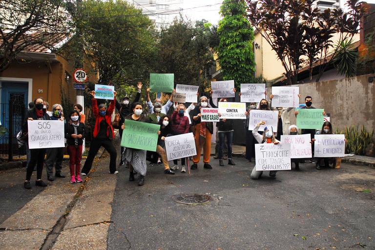 grupo com cartazes de papel, em frente a rua com casinhas
