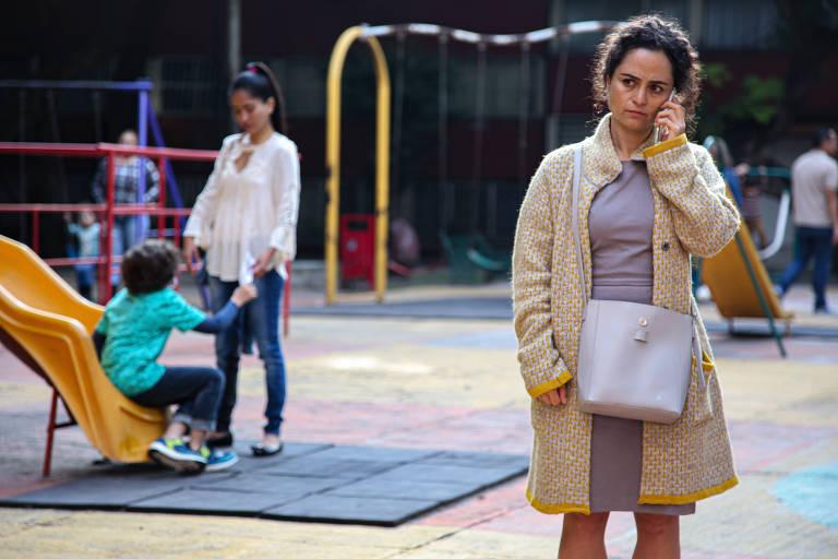 mulher branca fala ao telefone diante de parquinho infantil