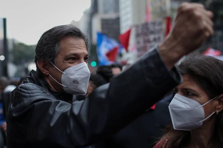 Fernando Haddad levanta o punho enquanto atravessa multidão.