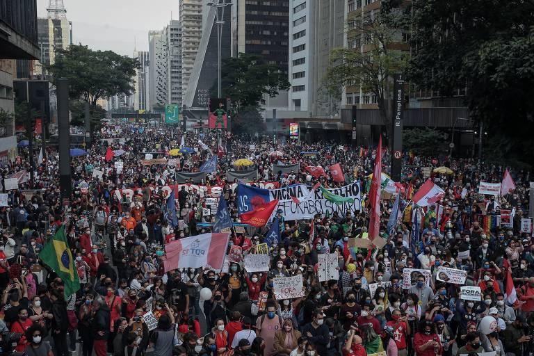 Vista do alto, concentração de manifestantes carregando bandeiras e cartazes na avenida Paulista.