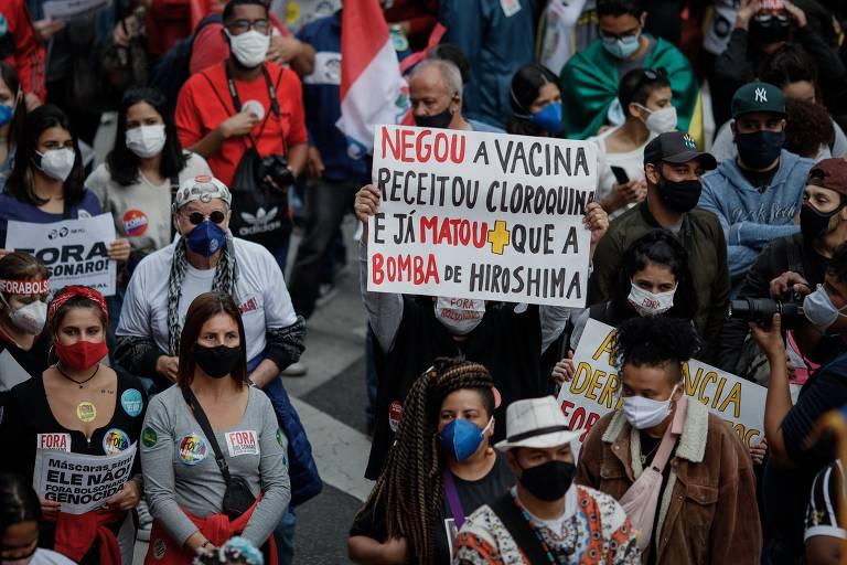 """Manifestante carrega cartaz onde está escrito """"Negou a vacina, receitou cloroquina e já matou mais que a bomba de Hiroshima"""", em meio a multidão."""