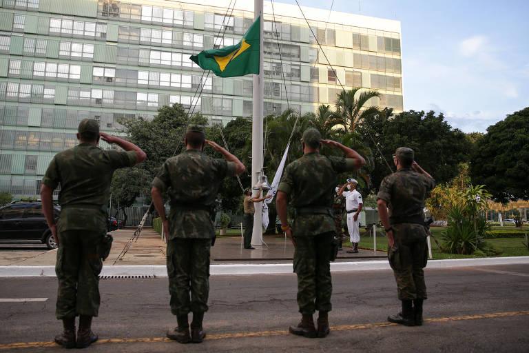 Militares fazem a cerimônia de descerramento da bandeira, em frente ao Ministério da Defesa, em Brasília (DF)
