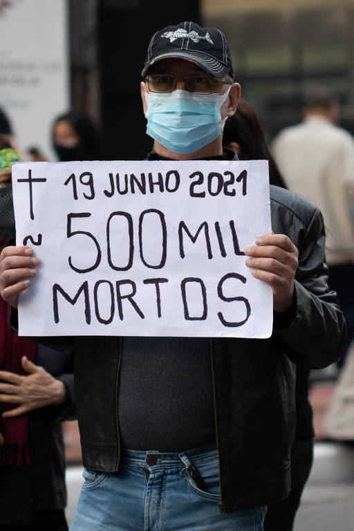 """homem segura cartaz com cruz desenhada e as palavras """"500 mil mortos"""""""