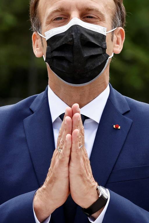 Macron, de máscara, une as mãos como se rezasse