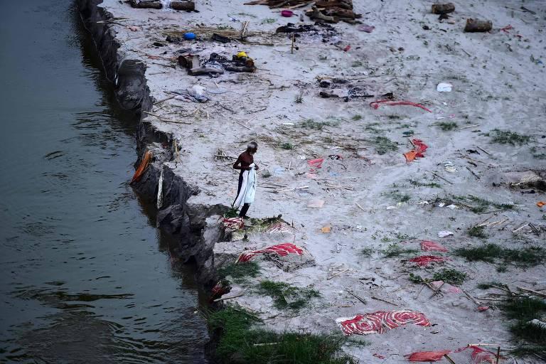 Homem em meio a covas às margens do rio Ganges em Phafamau