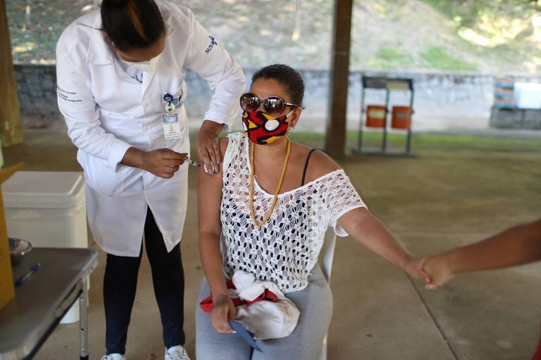 Uma mulher sentada e de máscara, estica o braço e segura a mão de uma pessoa que está fora da cena. No outro lado dela, um enfermeiro, de pé, aplica uma dose da vacina